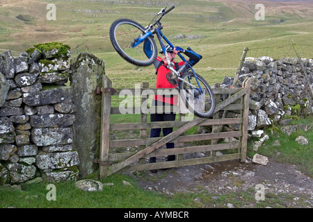 Cyclist lifting his bike over a fence during Mountain Bike trip in Yorkshire Dales, Great Britain - Stock Image