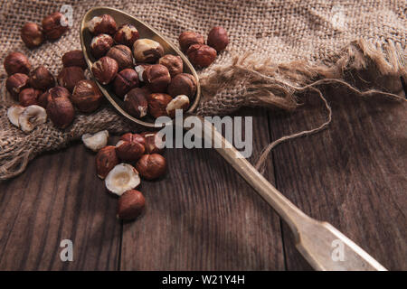 Hazelnuts on an old spoon and composition from old wood and material - Stock Image