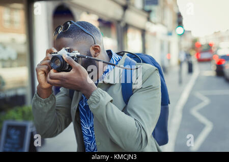 Young male tourist photographing with camera on street - Stock Image