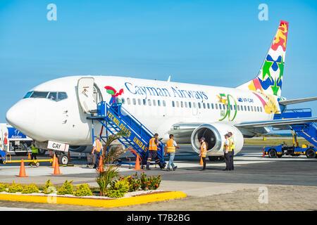 Ground crew prepares Cayman Airways aircraft for departure at Juan Manuel Galvez Airport Roatan Honduras. - Stock Image