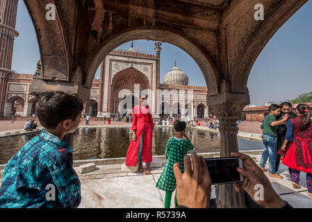 A girl posing for a photo in front of the pool of Jama Masjid mosque, Old Delhi, India - Stock Image