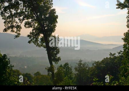 Mountains draped in low lying cloudy mist as seen from an overlook at daybreak - Stock Image