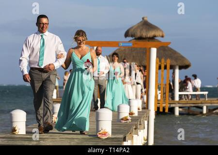 Just Married Couple walking on Fishing Dock Pier after the Tropical Beach Wedding Ceremony in Caye Caulker Belize - Stock Image