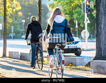 Strasbourg, Alsace, France, rear view of 2 women biking on pavement, - Stock Image