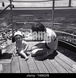 1960s, cruise, mother on a ship with young baby. - Stock Image