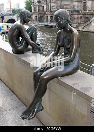 Three girls and a boy by Wilfried Fitzenreiter - Statue by the Spree River, Moabit, Berlin, Germany,side view sitting - Stock Image