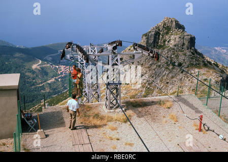 1960s, two tourists standing in the mountain chair lift or cable car, high up on the top of Mount Capanne, Elba, Italy. The 'cable car' or basket lift is a metal cage that one stands in for the ride to the top or bottom and like a sking chair lift one has to hop into and the attendant as seen in the picture here closes the 'door' and you are on your way. - Stock Image