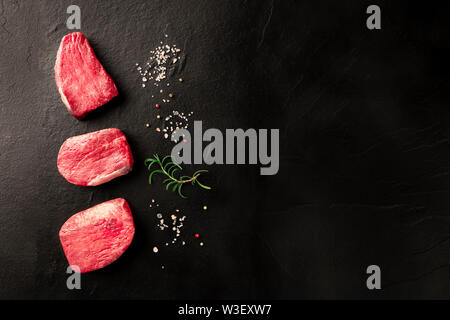Raw sirloin beef steaks with salt, pepper and rosemary on a black background with copy space - Stock Image