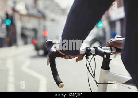 Hands on man on bicycle handlebars, commuting on sunny urban street - Stock Image