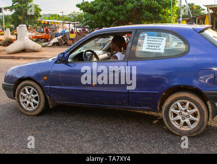 Young african driver asking people to be indulgent with her, Région des Lacs, Yamoussoukro, Ivory Coast - Stock Image