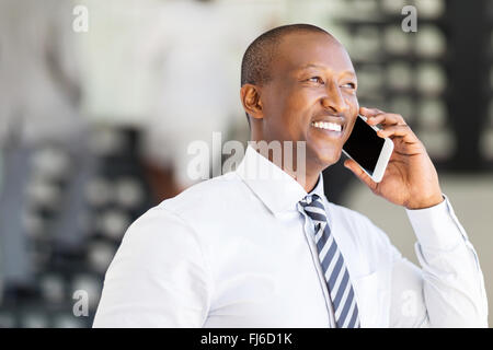 modern African corporate worker talking on cell phone in office - Stock Image