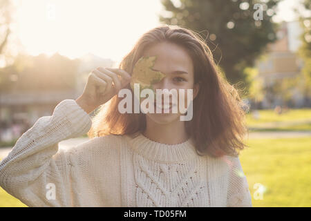 Portrait of European charming teen girl. She keeps yellowed fallen maple leaf. Model poses in rays of sunset and sun glare. Flecks of sunlight. Face t - Stock Image