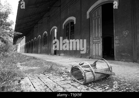Crushed antique wood barrel at the abandoned Canfranc International railway station (Canfranc, Pyrenees, Jacetania, Huesca, Aragon, Spain).B&W version - Stock Image