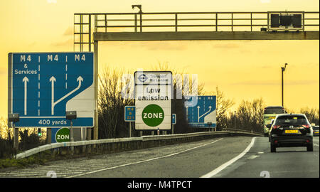 Low Emission Zone signpost next to the hard shoulder by Transport for London TFL, plus lane signs on the M4 motorway - Stock Image