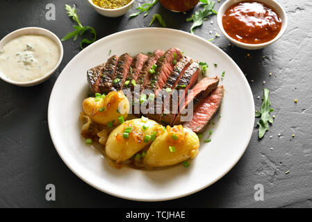 Boiled potato with medium rare roast beef over black stone table - Stock Image