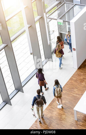 Female and male university students leaving by university lobby entrance - Stock Image