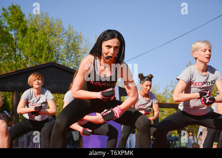 Nis, Serbia - April 20, 2019 Group of woman practicing pose under control of female Piloxing teacher outdoors - Stock Image