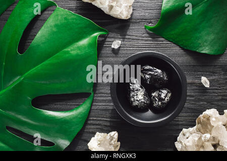 Apache Tears with Smoky Quartz and Monstera on Black Wood - Stock Image