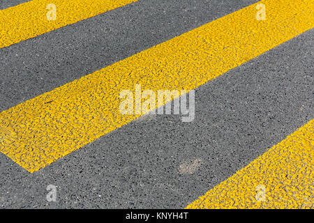 A sign on the roadway marked with a zebra protects people who cross the street. - Stock Image