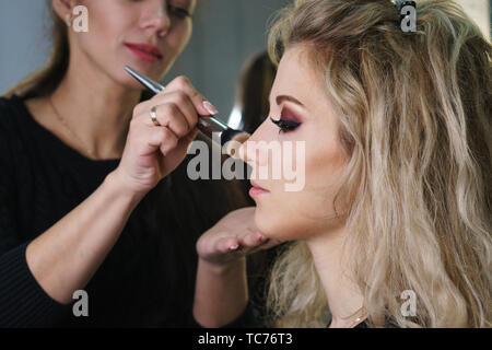 Make-up artist working in make-up studio, applying makeup on face of female clients. Makeup artist evens tone facial makeup brush. Evening make-up. - Stock Image