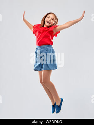 happy smiling girl in red shirt and skirt jumping - Stock Image