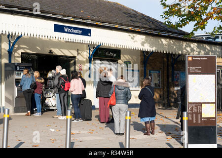 Commuters at Winchester train station queuing for tickets at a ticket machine - Stock Image