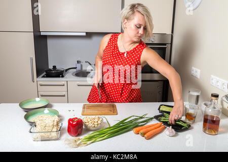 Girl reaching for asparagus and holding knife in other hand - Stock Image