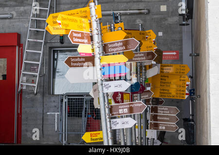 Many Swiss hiking signposts with overlapping signs stored for later reuse. - Stock Image