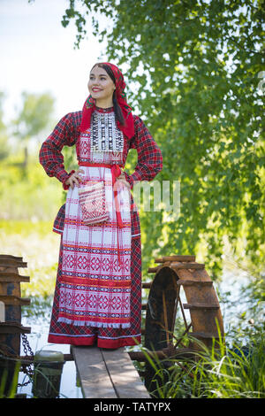 Young woman in scarf and traditional russian clothes stands on a small pier near the lake, and holds hands on a waist, vertical view - Stock Image