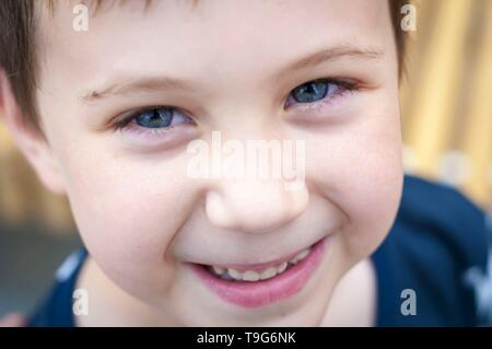 Elementary school age blue eyed Caucasian child boy looking at the camera closeup image. Smiling boy closeup portrait, positive attitude, happy - Stock Image