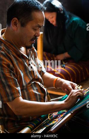 Man weaving traditional Bhutanese textiles on back-strap loom in Thimphu, Bhutan - Stock Image
