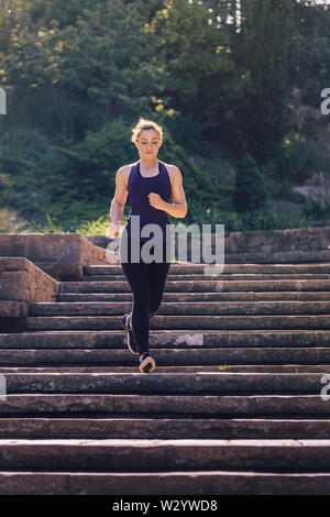 young sporty girl running downstairs in the morning on the stairs of the park, morning workout outdoors, sports and healthy lifestyle - Stock Image