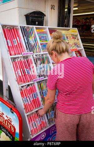 UK, England, Lancashire, Blackpool, Promenade, woman customer at traditional seaside rock shop - Stock Image