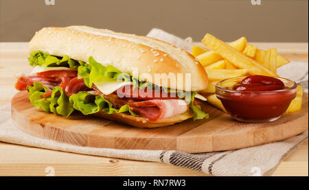 Fresh submarine sandwich with cheese, bacon, tomatoes and lettuce, on light wooden background - Stock Image
