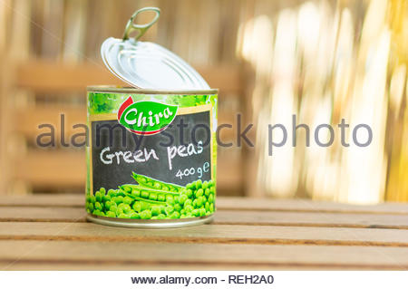Poznan, Poland - October 10, 2018: Chira green peas in a open 400 gram can on a wooden table - Stock Image