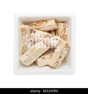 Pieces of nougat candy in a square bowl isolated on white background - Stock Image
