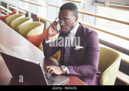 A beautiful stylish African American businesswoman wearing a suit uses his laptop while working - Stock Image