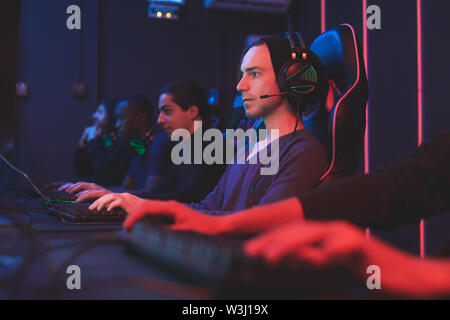 Serious concentrated gamers in headphones for online communication sitting in dark room of computer club and using computers for network games - Stock Image