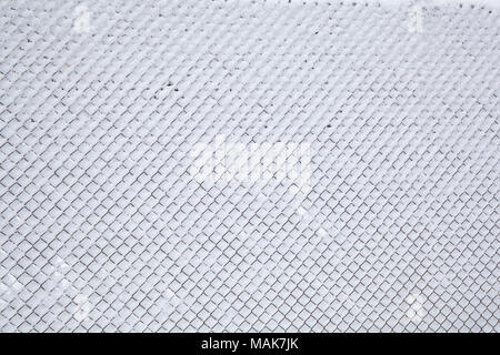 Snowy metallic fence net after snowfall as background - Stock Image
