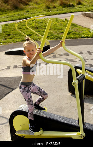 Six year old girl, on a cross trainer machine in a free to use outdoor fitness area - Stock Image