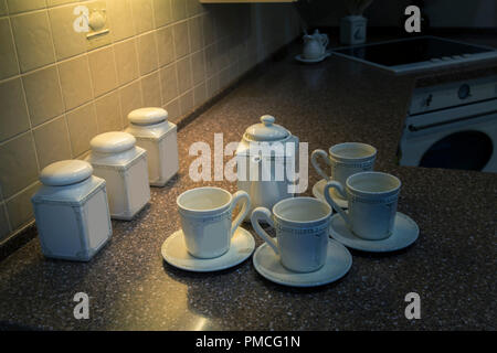 Tea set from white porcelain on a table illuminated with artificial light - Stock Image