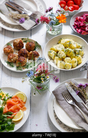 Scandinavian midsummer feast with potato salad, meatballs, salmon and beetroot - Stock Image