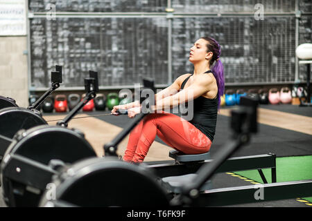 Young woman working out exercising on a rowing machine inside a professional gym during training in a health and fitness concept viewed from behind a  - Stock Image