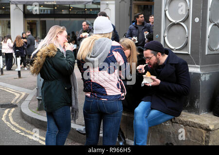 Young people eating standing on Stoney Street outside Roast Restaurant Floral Hall in Borough Market, South London England UK  KATHY DEWITT - Stock Image