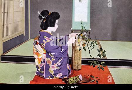 A Japanese woman practising Ikebana, the traditional Japanese art of flower arranging. - Stock Image