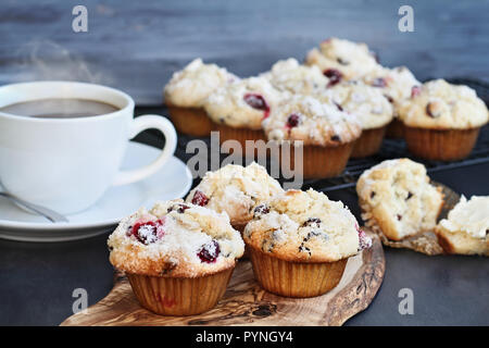 Cranberry Muffins on a wood cutting board with more cooling on a bakers rack. Extreme shallow depth of field with selective focus on center muffin. St - Stock Image