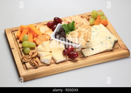 Mix cheese on a oard with some fruits on the side - Stock Image
