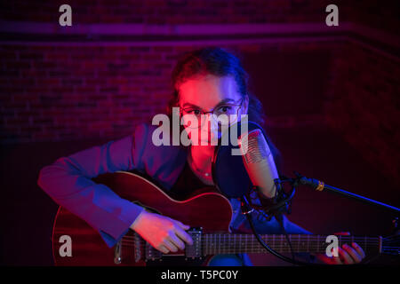 A young woman in glasses playing guitar and singing by the mic in neon lighting - Stock Image
