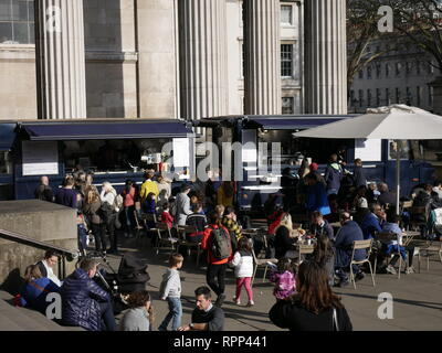 The British Museum, Russell Street, London, England. Busy seated area with tables and chairs for eating from the food vans. - Stock Image