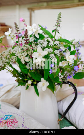 mixed wildflowers in white metal jug - Stock Image